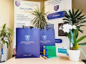 Na zdjęciu znajdują się dwa złote indeksy oraz torby prezentowe z logo MUP Oświęcim, a wtle widoczne sa rollupy uczelniane.