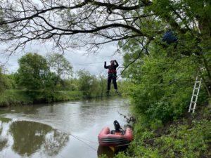Student Ratownictwa medycznego uczy się przechodzić nad rzeką na linie rozwieszonej pomiędzy drzewami.