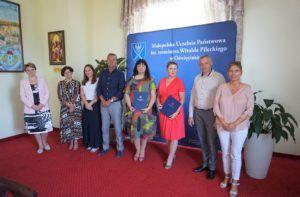 Na zdjęciu, na tle ścianki promocyjnej znajduje się 7 osób, które były obecne podczas uroczystego podpisania umowy o współpracy.