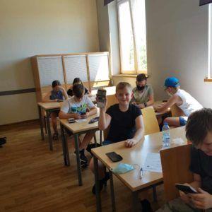 Na zdjęciu grupa dzieci siedzi przy biurkach, a jeden chłopiec unosi do góry kalkulator graficzny.