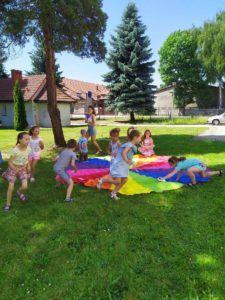 Grupka dzieci bawi się na trawie chustą edukacyjną.