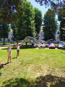 Dwie dziewczynki puszczają przed budynkiem Uczelni bańki mydlane.