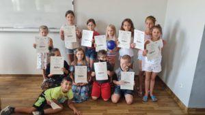 Grupa dzieci uczestniczących w projekcie Oświęcimski Uniwersytet Mlodego Odkrywcy stoi i pozuje do ostatniego wspólnego zdjęcia z dyplomami ukończenia projektu w rękach