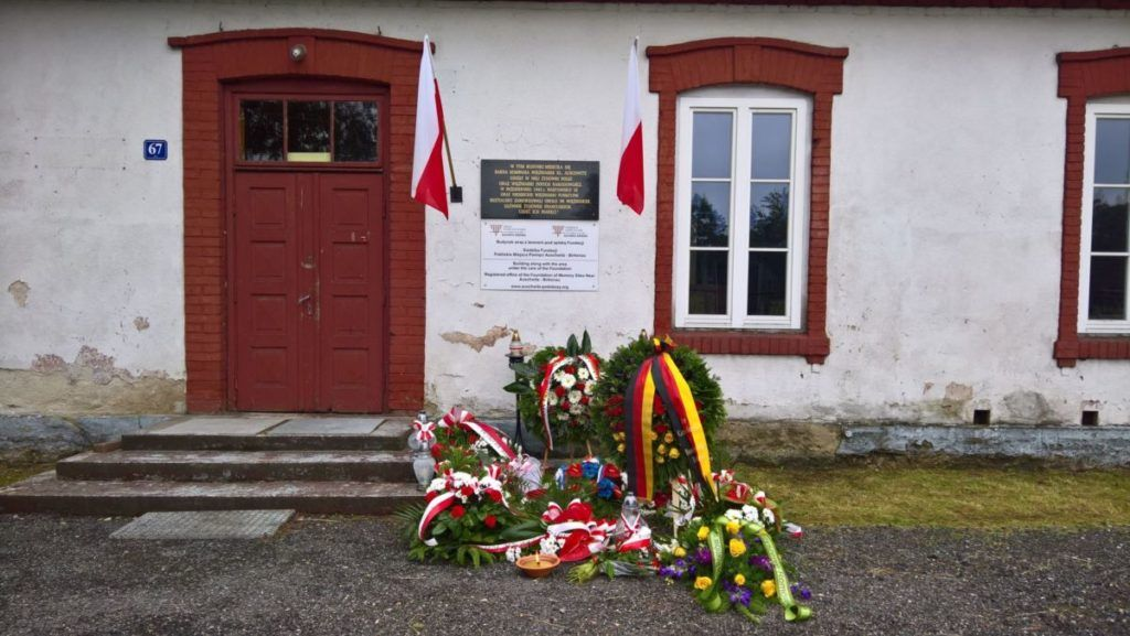 Na zdjęciu fragment budynku, na którym znajduje się pamiątkowa tablica utworzenia Karnej Kompanii Kobiet, po prawej i lewej stronie tablicy powiewaja flagi RP, a pod tablicą leżą złożone przez delegacje wiązanki kwiatów i znicze.