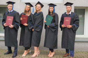 Na zdjęciu 5 studentów ubranych w togi absolwenckie, trzymaja w rękach swoje prace dyplomowe