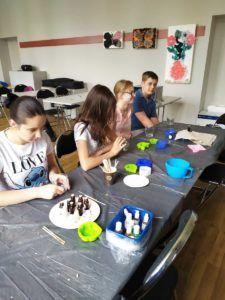 Młodzież siedzi przy stole i tworzy mydła i świece