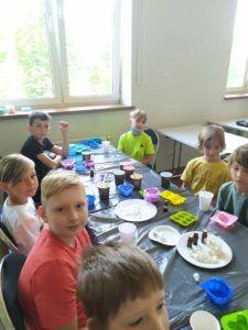 Dzieci w trakcie zajęć z tworzenia mydeł i świec pozują do zdjęcia