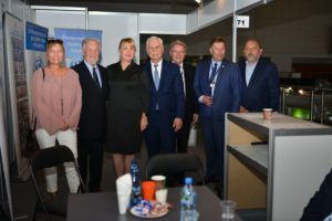 5 mężczyzn i 2 kobiety stoją przy stoisku wystawienniczym i pozują do zdjęcia