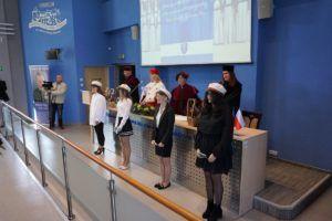 Władze Uczelni wraz z czterema studentkami immatrykulowanymi stoją w Auli i spiewają pieśń.