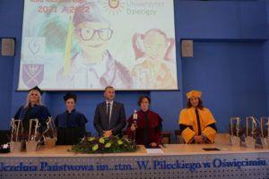 Zastępca Prezydenta miasta Oświęcim, Pani Prorektor oraz trzy nauczycielki akademickie pozują do zdjęcia za stołem prezdialnym w Auli Uczelni w trakcie Inauguracji Roku Akademickiego Oświęcimskiego Uniwersytetu Dziecięcego
