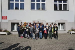 Grupa dzieci i dorosłych pozuje do zdjęcia przed budynkiem Uczelni